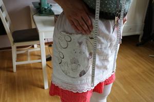 Förklädet sitter alltid på när Annastina jobbar. Och runt halsen finns måttband och sax.