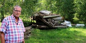 Hans-Göran Björk står framför kommunens gamla bryggor på parkeringsplatsen vid Laksjöbadet i Harbo. Engagerade i badet vill att det ska vara välkomnande och därmed att kommunen fraktar bryggorna till soptippen.