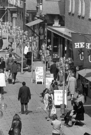 Det saknas uppgifter om denna bild från Prästgatan i ÖP:s arkiv. Den är i alla fall från de yviga frisyrernas  och de utsvängda jeansens tidevarv. På grundval av dessa antaganden torde bilden vara från tidigt 1970-tal. Till höger finns i dag en blomsterhandel och skoaffär. Bortom ser man Wedemarks karaktäristiska logotype.