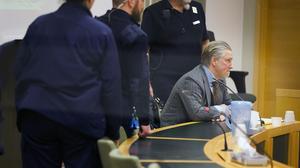 Simon Kosha är skymd av häktespersonalen, den som synd på  bilden är hans försvarare, advokat Richard Larsson.