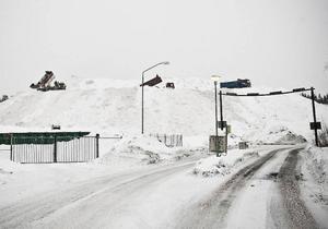 Lastbilar går i skytteltrafik till och upp på snötippen i Odenskog där det ligger 300 000 kubikmeter snö. För att inte snöberget ska kalva som en glaciär besprutas snön med vatten för att hårdgöra berget. Någon gång i september kan snöberget ha smält ned.