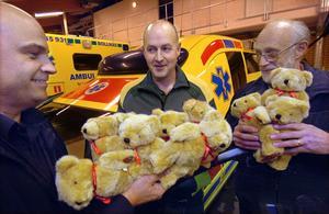 Odd Fellows representanter P.O Moberg och Olle Carlsson lämnar över nallebjörnarna till Bengt Englund vid ambulansen i Bollnäs.