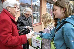 Majblommeförsäljningen har startat. Maud Gustafsson köper majblomma av Tove Olofsson, den sista som hon har. I bakgrunden är det Britta Svensson som köper av Jonna Major.