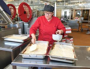 Full rush i produktionsköket tidigt på förmiddagen. Kocken Anita Åberg ser till att rätt mängd bechamelsås tillsätts i lasagnen.