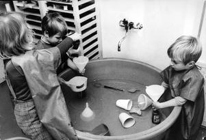 Olika åldrar samsas fint i det kombinerade halvdaghemmet-lekskolan Trossbacken på Viksäng. Åsa Lövgren, i mitten, sex år och alltså bland de äldsta lekskolebarnen, leker i vattenbaljan med tvillingarna Maria tv och Mats Eskilsson, som är fyra år och hör till halvdaghemmets yngsta.  31 oktober 1968.