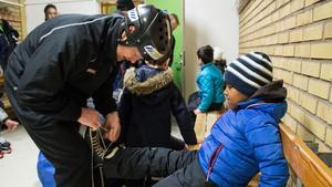 7-årige Abdiqafar Hussein får hjälp av Johan Berger att få på sig skridskorna.