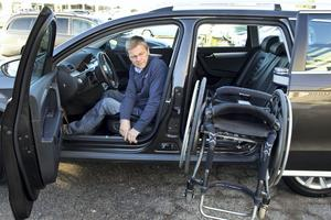 Roger Eriksson trycker på en knapp på förardörren och då öppnar sig bakdörren. En arm kommer ut och tar tag i rullstolen, som är av kolfiber och väger fyra kilo. Armen svänger sedan in och placerar rullstolen i baksätet.