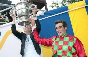 Grand national-segraren Edouard Monfort lyfter Topham-pokalen. Till vänster vinnarhästen Glückstags ägare Elfie Schnakenberg.