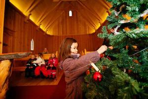 Dagisbarnen fick hjälpa till med att klä julgranen. Här är det Isabelle Nilsson som hänger upp en röd kula.