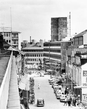 Smedjegatan juli 1958. Fotot är taget från det hus som låg där Igor ligger idag. I bakgrunden ses bygget av Folkets hus. Fotodatum: 1958-07-29