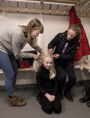 Nora Alm får håret fixat. Assistenter är tränaren Sophie Forsberg och storasyrran Hannah.