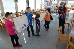 Elever från Tulpanens skola håller upp diagram medan rektorn Elisabeth Berg berättar hur lite mat barnen slängt.