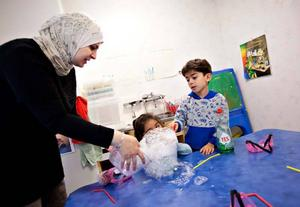 NATURVETENSKAP OCH SPRÅK. Modersmålsläraren Hanan Abu Moh'd assisterar och fyller ut språket när Tasnim Abu Amara och Ali Houssein experimenterar.