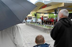 Paraply eller inte? Det var lite valfritt på torget i Laxå, där det föll tunga regndroppar stundom men inte i någon större mängd.