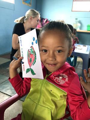 En stolt Layla visar upp den teckning hon ritat med de nyinköpta pennorna.