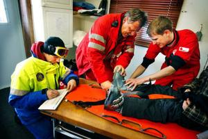 Janne Jonsson och Jörgen Nilsson från Röda Korset hjälper henne av med pjäxan. Pistören Mikael Höglund skriver en skaderapport.