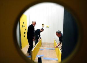 Arbetet med utställningen om de  tjugo år Fem-i-tolv-rörelsen i Härnösand har funnits, var i full gång tidigare i veckan. Fotografen Samir Hussein och Stig Wallin, ordförande i rörelsen sedan länge, ger snickaren Leo von Euler en hjälpande hand.