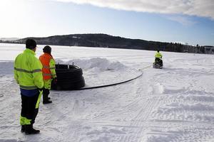 Med hjälp av snöskoter dras vattenledningen ut.