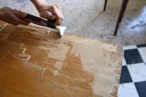 Anna Löfstrand använder sig ofta av en skrapa för att ta bort gammal ytbehandling från möblerna. Här från en liten lackad byrå.