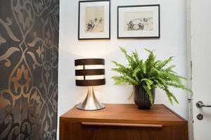 Lampskärm med ränder i brun metall på byrå i teak.
