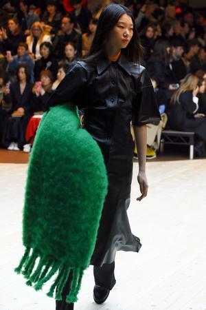 Att bära med sig en hel yllefilt, som en modell gör på Celines catwalk, är ingen dålig idé i vinterkalla Sverige.