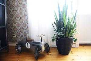 En leksaksbil kompar fint mot den gamla klassiska tapeten i vardagsrummet.