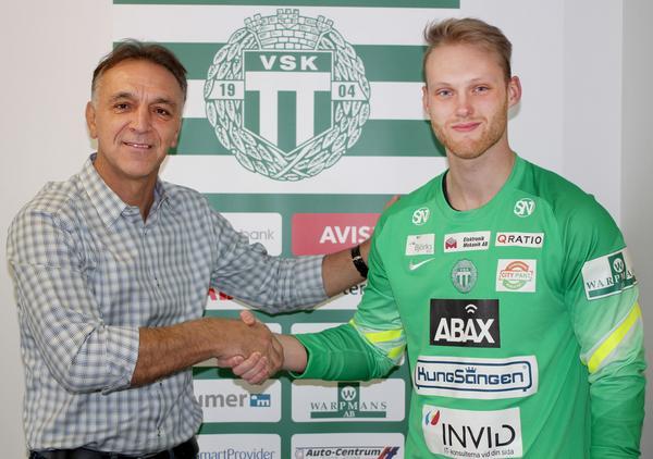 En av VSK Fotbolls sportsligt ansvariga, Ado Sadzak, skakar hand med Alexander Lundin efter att målvakten presenterats av Grönvitt.