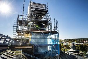 Bakom byggnadsställningarna runt tornet på Hedbergska skolans tak kan man skymta stjärnan i toppen.