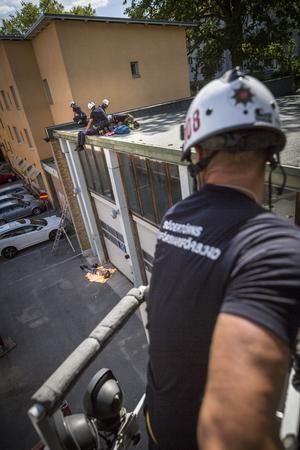 Under övning har två personer skadats. En har fallit ner från taket och en (Andreas Malmström) ligger skadad kvar där uppe. Styrkan kan inte bära ner honom för stegarna, så Roger Lindgren kör upp hävaren till taket.