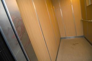 På torsdagen fanns fortfarande tydliga blodfläckar kvar på insidan av hissen i trappuppgången där en lägenhet spärrats av.