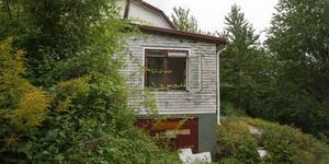 Bostadshusets fönster är antingen igenspikade med spånskivor eller sönderslagna.