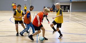 6B Nyckelbergsskolan (gula västar) spelar mot 6A-C på S:t Olovsskolan (orange västar). Liam Magnusson försöker hindra Neo Sallantos framfart.
