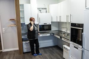 Boendehandledare Snöfrid Eriksson ser bara fördelar med sin nya arbetsplats. Lokalerna erbjuder bättre hjälpmedel för såväl de boende som personalen. Här visar hon hur köksinredningen går att sänka ned med ett knapptryck. Samtidigt ringer telefonen, det är mycket som ska hinnas med innan allt är i sin ordning.