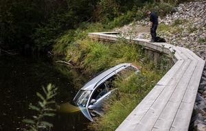 Bilen körde av vägen genom en passage mellan ett vägräcke och ett staket – och hamnade i ån.