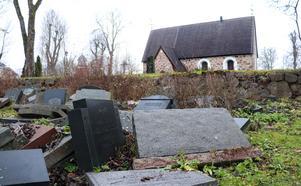 Gravstenarna ligger slängda bakom kyrkomuren.