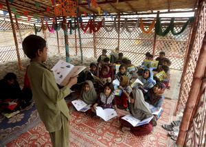 Pakistanska flickor och pojkar i en skola i Lahores fattiga kvarter. Fortfarande går miljoner flickor i Pakistan inte i skolan, enligt Human Rights Watch. Foto: AP Photo/K.M. Chaudary