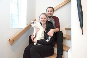 Josephine Hellberg och Max Lestander sitter med katten Kimmy i trappan i sitt nya hus i det nya villaområdet i Spånbro och stormtrivs.