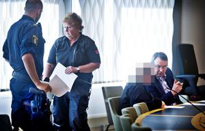 Bild från söndagens häktningsförhandling där den misstänkta kvinnan pratar med sin försvarare efter att Västmanlands tingsrätt beslutat att häkta henne på sannolika skäl misstänkt för mordbrand och grov mordbrand i tre fall.