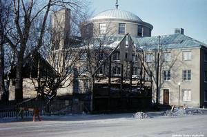 Början av 1960-talet.  Den gamla byggnaden närmast konserthus/bibliotek rivs. Här, vid Fabriksgatan,  ska så småningom det nya riksbankshuset byggas. Fotograf: Karl Andersson.  (Bildkälla: Örebro stadsarkiv)