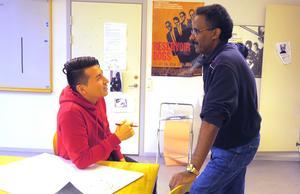 Murtaza diskuterar med läraren Suleiman hur han ska färglägga en klocka i sin målning.