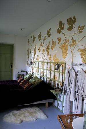Den romantiska sovrummet är perfekt för bröllopspar. Guldlöven målade Ernst dit med hjälp av schabloner.