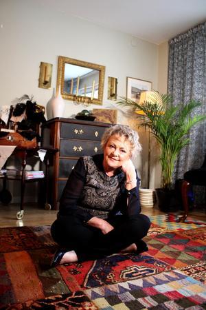 Gunmari Palmquist på sin nyfyndade matta som hon köpte på auktion i Surahammar. Mattan är ett lapptäcke av andra gamla mattor.