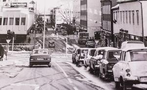 Stora gatans korsning med Hållgatan får ett helt nytt utseende när cityringen byggs om 1986-87. Trafiken i Oxbacken dubbelriktas. Huset till höger på bilden rivs för att ge plats åt