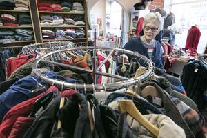 Anna-Britt Karström sorterar kläder. I lokalen finns även en fikahörna som brukar vara välbesökt.