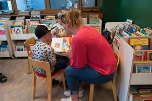 Matilda Jansson läser för sonen Algot på invigningen av Grängesbergs bibliotek nya lokaler.