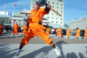 Bild: Pernilla Wahlman Datum: 20051021 Med rökelse, böner och slagkraftig kung fu invigdes Dragon Gate i Älvkarleby. 22 orangeklädda buddhistmunkar intog torget framför hotellet. Tillsammans med sin ledare Shaolinmästaren, Mao Younghan, 73 år, utförde de en invigningsritual vid buddhastatyn. Ritualen skedde i helt tystnad