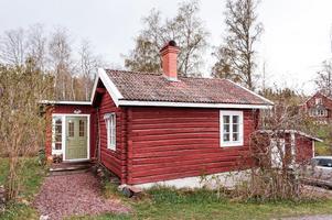 Timrat fritidshus med falurött och vita knutar. Sjöutsikt. Foto: Kristofer Skog.