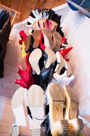 Mängder av klackskor, espadrillos och träskor hänger på en speciell skoställning i ena hörnet.