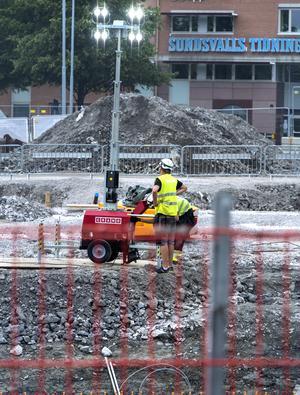 Strålkastare monteras upp för att betongarbetarna ska kunna se bra under kvällen och nattens slipningsarbete.