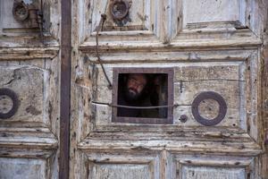 En präst kikar ut genom ett litet fönster i porten till Heliga gravens kyrka i Jerusalem.